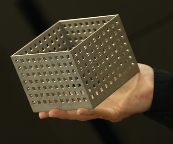 A perforated metal box produced by an Arcam 3D printer.