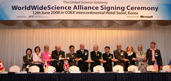 WWS Alliance members in a row with arms criss-crossed in front of them shaking hands with those on either side