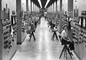 1960s - women at work sitting on stools in a long wide hallway