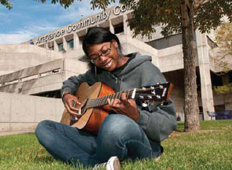 A student enjoys music on the Littleton Campus lawn