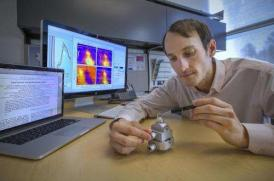 Brookhaven National Laboratory (BNL) researcher Ignace Jarrige shown with the sample used in the magnetic refrigeration experiment. Courtesy BNL