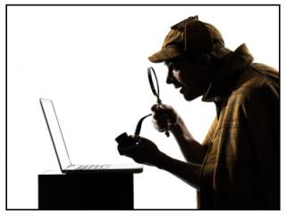 Man with pipe, deerstalker cap, and magnifying glass looking at a computer.
