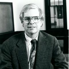 Kenneth Geddes Wilson. White man with white hair wearing glasses and a dark suit and tie.