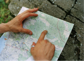 A person uses their hands to gesture at a road map.